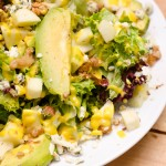 Delicious salad with avocado, green apple, blue cheese and walnuts along with honey and mustard dressing